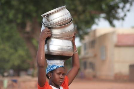Girl cqrrying cooking pots in Segou